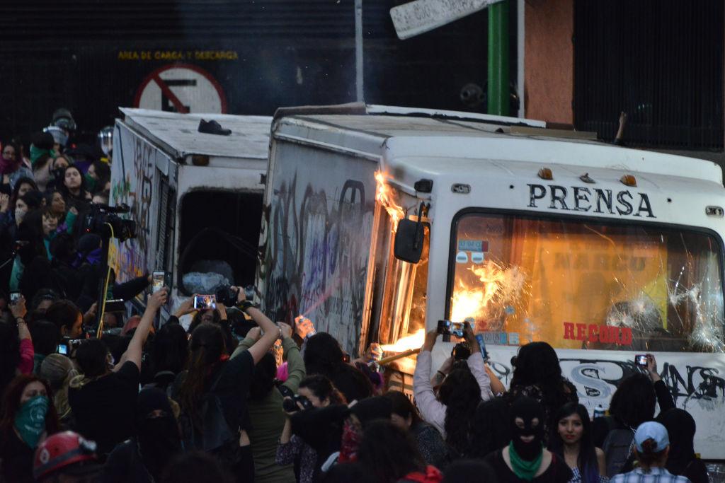 Manifestantes contra el femicidio queman un vehículo de la prensa en México