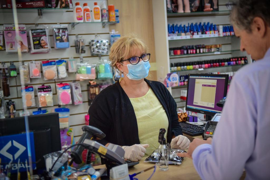Una trabajadora farmacéutica utiliza una mascarilla para atender público en Uruguay