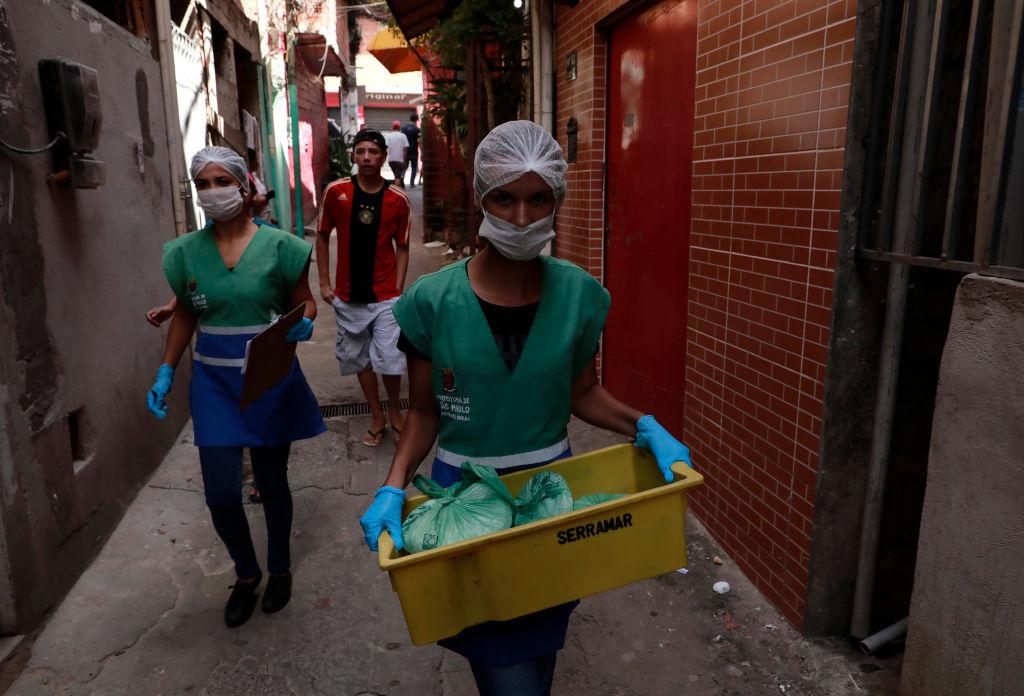 Unos voluntarios entregan alimentos a los habitantes de la favela Paraisopolis en Sao Paulo