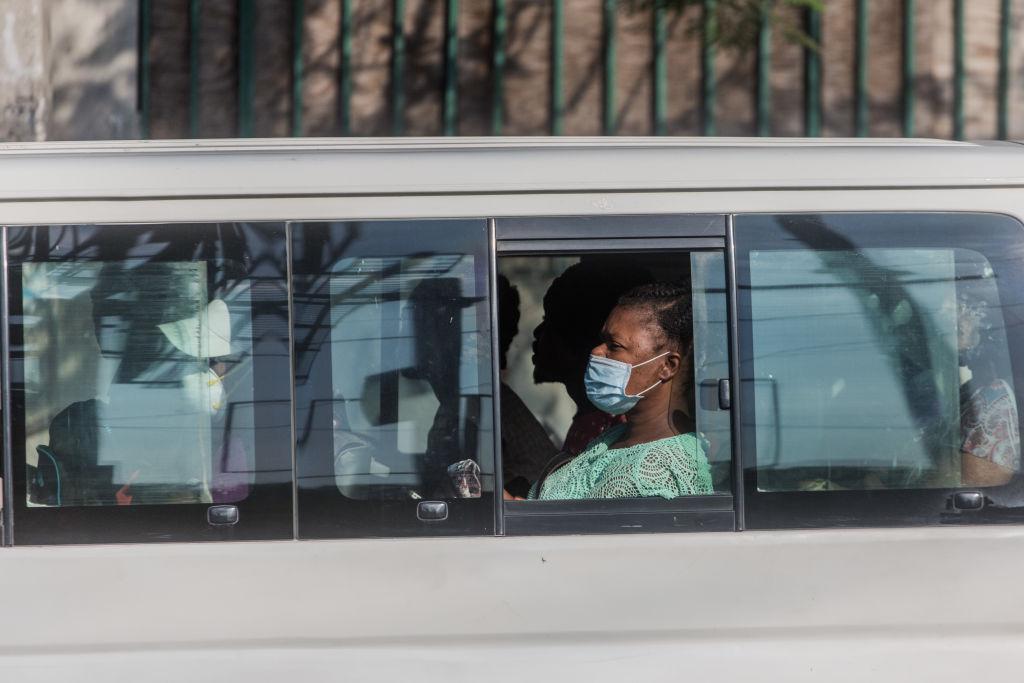 En Haití una mujer utiliza una máscara mientras es transportada en medio del brote de Covid-19