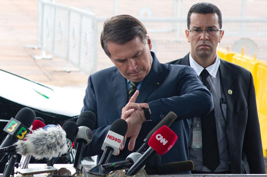 Jair Bolsonaro intenta ver la hora en una conferencia en Brasilia