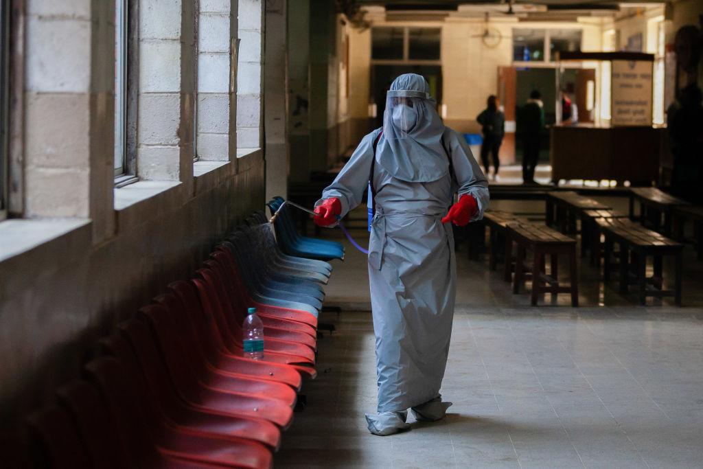Un funcionario de la salud higieniza los pasillos de un hospital en Nepal