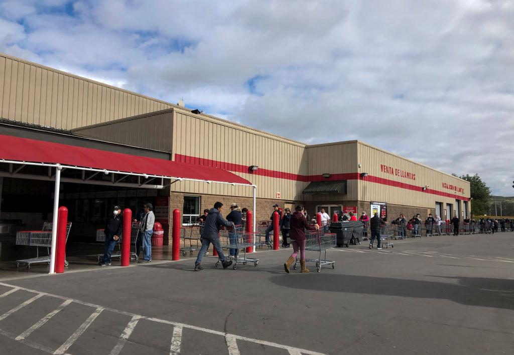 Los ciudadanos mexicanos hacen una fila para ingresar a un supermercado en Tijuana