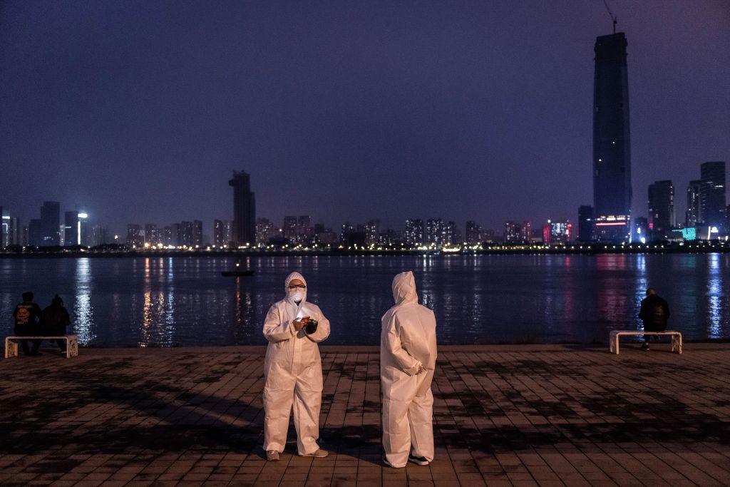 Un par de ciudadanos chinos se fotografían con trajes sanitarios en una plaza de la ciudad de Wuhan