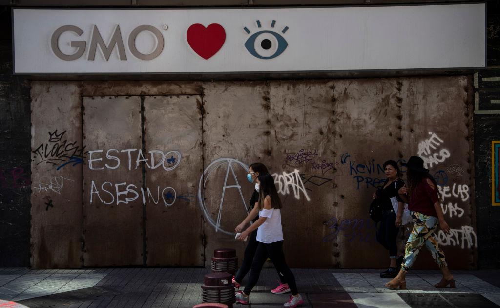 Una mujer camina por la ciudad de Santiago utilizando una máscara por el Covid-19