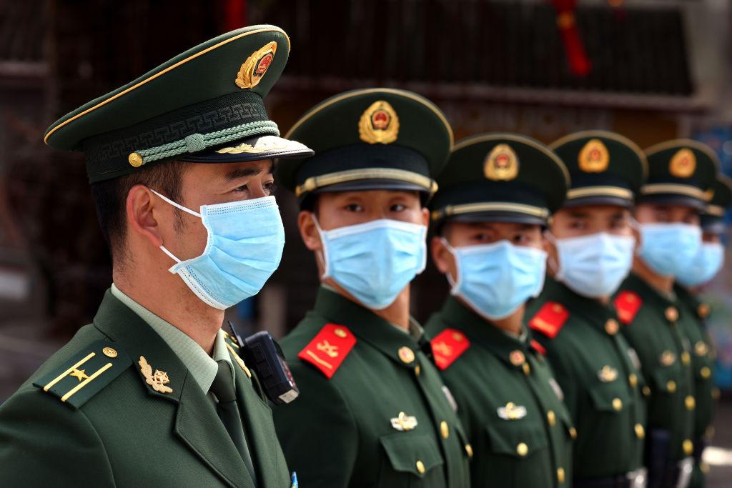 Un grupo de policías militares muestran el uso de mascarillas en China
