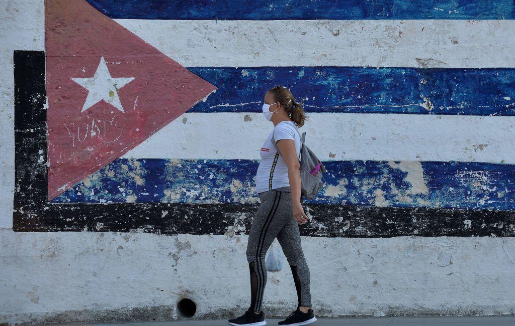 Una mujer utiliza una máscara mientras camina por la ciudad de La Habana