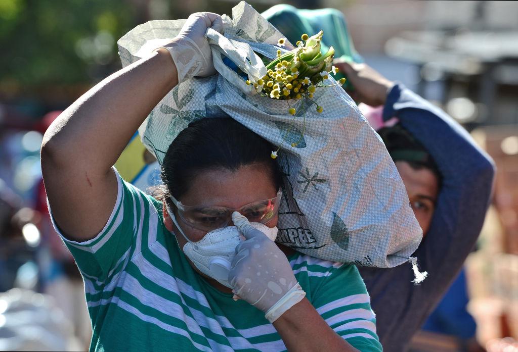 Una mujer con mascarilla sale a comprar alimentos en un mercado de la ciudad de Tegucigalpa