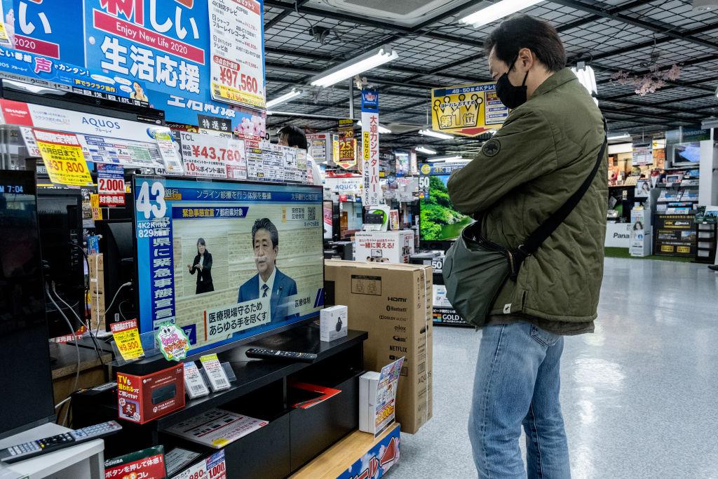 Una persona observa el mensaje del primer ministro japonés en una televisión