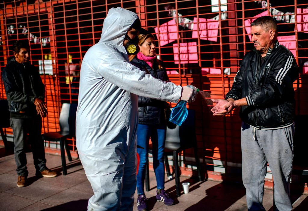 Un trabajador sanitario entrega alcohol a las personas en la municipalidad argentina de José Carlos Paz