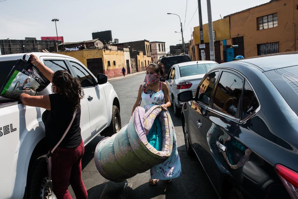 Una familia recibe donaciones en un barrio de la ciudad de Lima