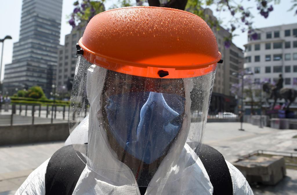 Un trabajador de limpieza utiliza un equipo especial para higienizar las calles de Ciudad de México