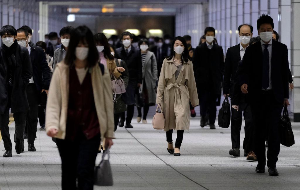 Los trabajadores utilizan máscaras en las calles de la ciudad de Tokio