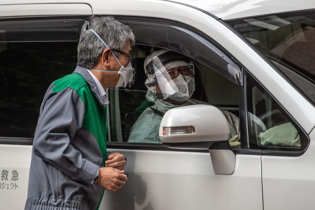 Un automovilista utiliza un traje completo de protección por el coronavirus en la ciudad de Tokio