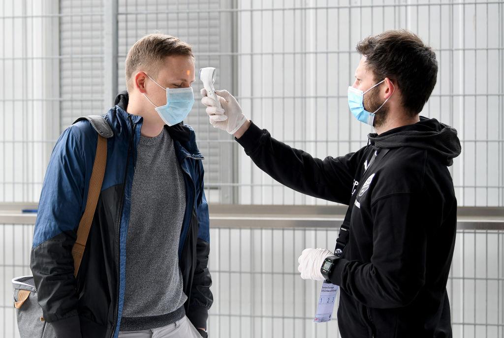 A un trabajador le miden la temperatura para ingresar a un estadio en Alemania