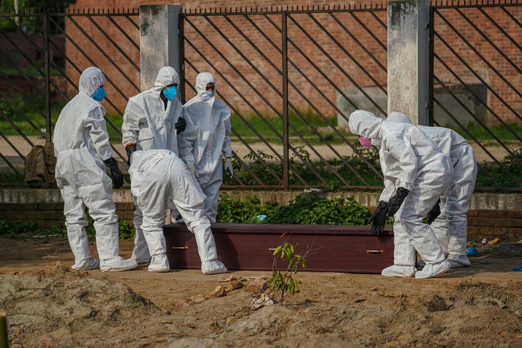 Trabajadores efectúan un funeral de una víctima del Covid-19 en Bangladesh