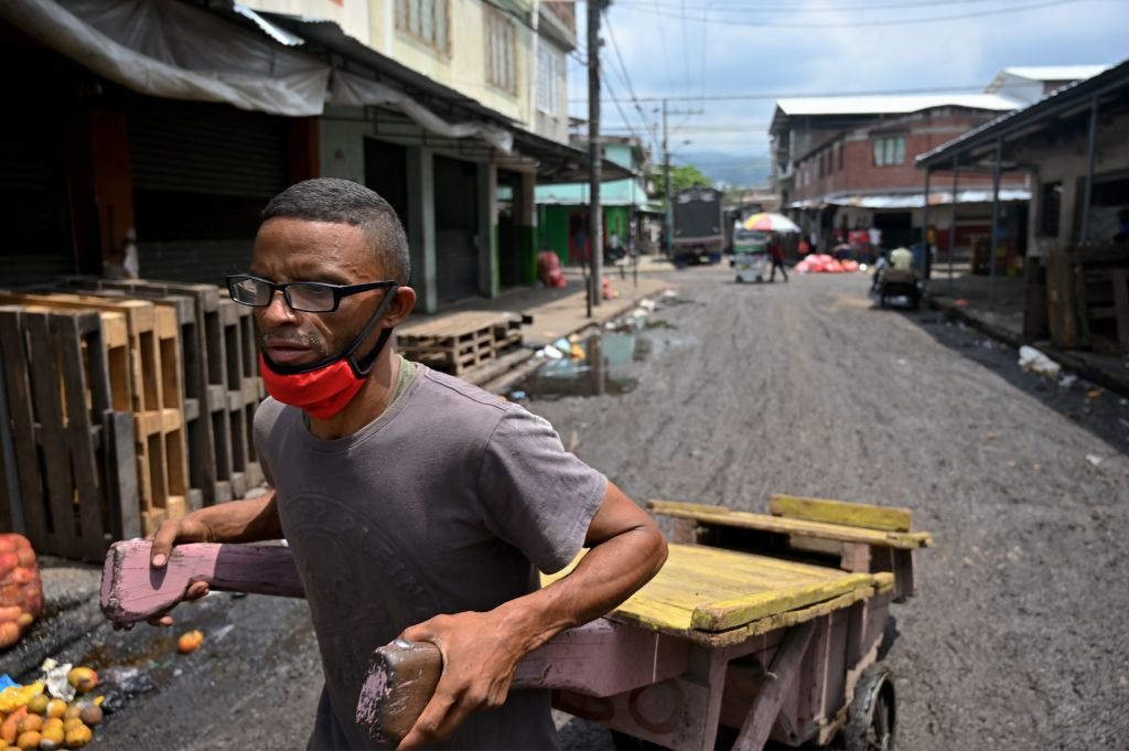 Un hombre traslada una carreta para trabajar en un mercado de Cali