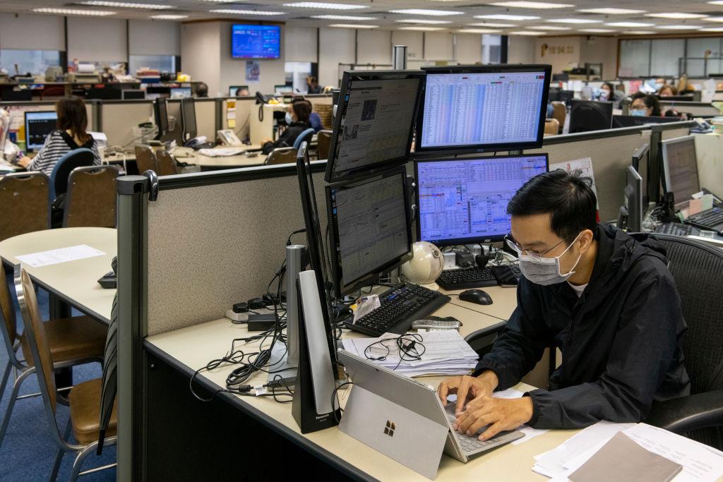 Un trabajador revisa el mercado bursátil en China