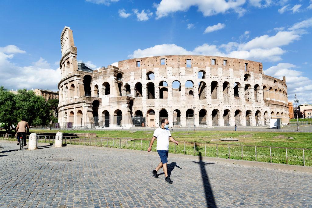 Un hombre con mascarilla camina frente al Coliseo de Roma
