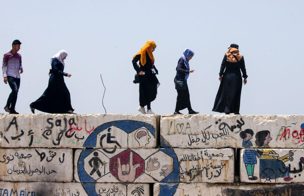 Mujeres palestinas caminan sobre muros en Gaza
