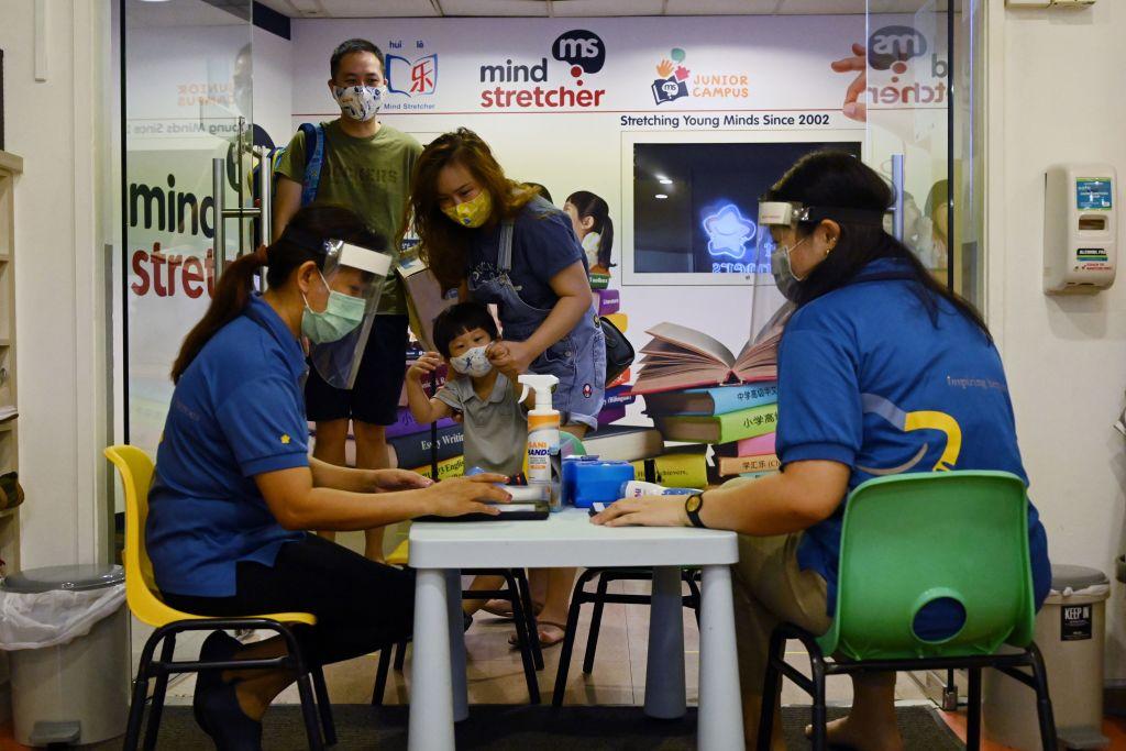 Los profesores toman las temperaturas de sus alumnos en Singapur