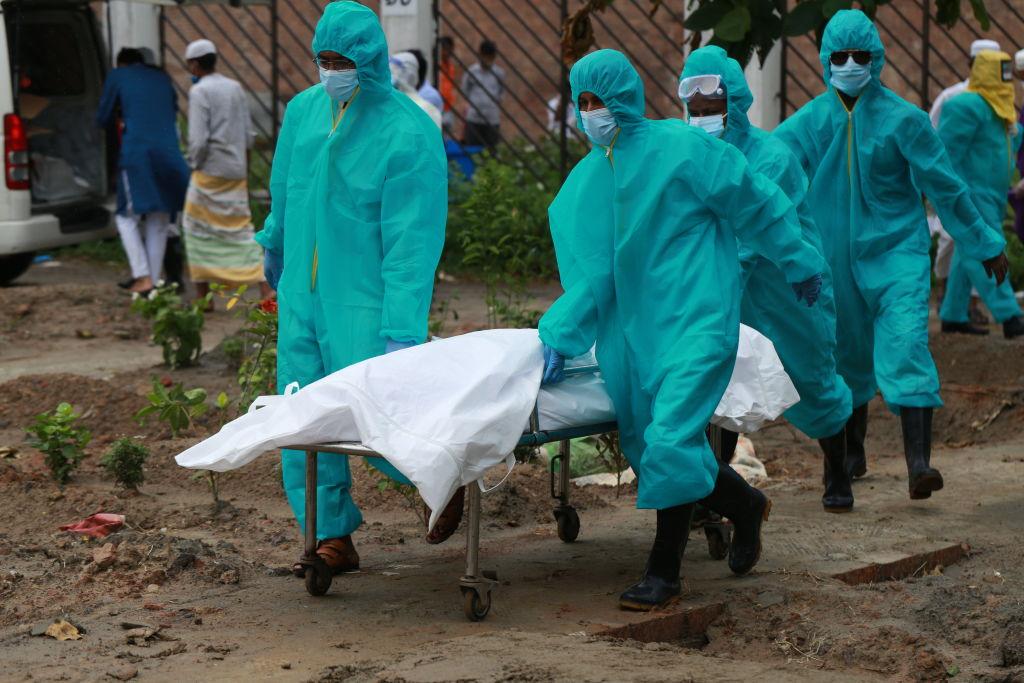 Trabajadores llevan a una víctima del Covid-19 en Dhaka