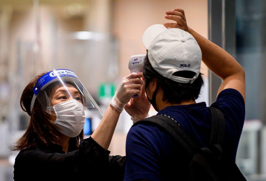 Trabajadora toma la temperatura de un cliente en Tokio