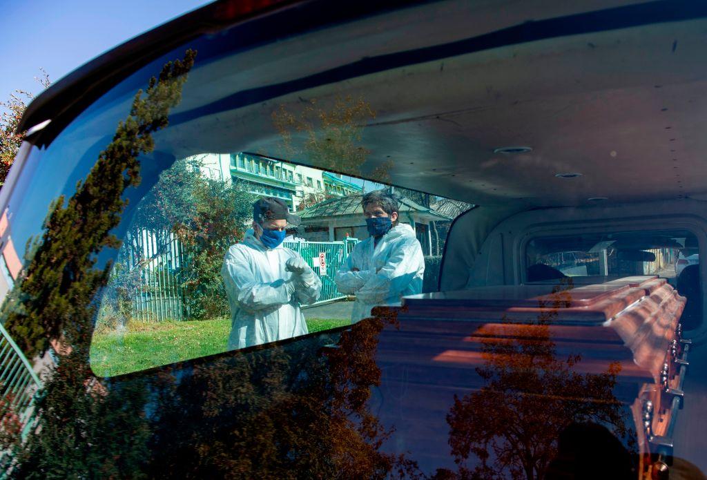 Trabajadores de una morgue observan una carroza fúnebre en Santiago