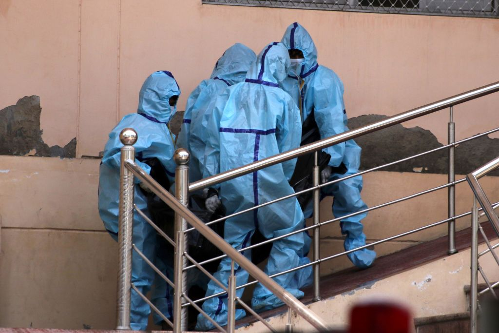 Una víctima del Covid-19 es llevada por trabajadores médicos en India