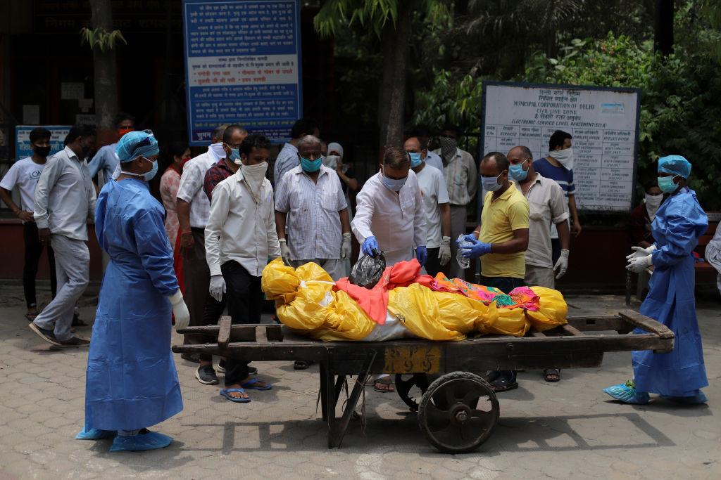 Trabajadores trasladan a una víctima del Covid-19 en Delhi