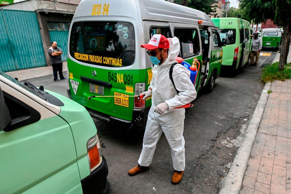 Trabajadores desinfectan buses del transporte público en México