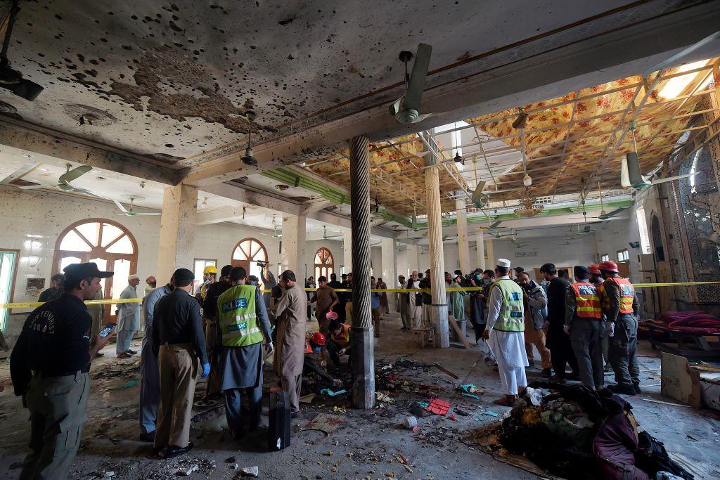 Oficiales y bomberos revisan la zona del ataque en Peshawar