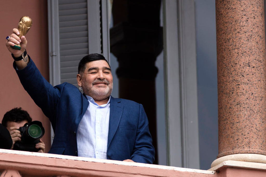 Diego Maradona saludando con una copa del mundo desde la Casa Rosada