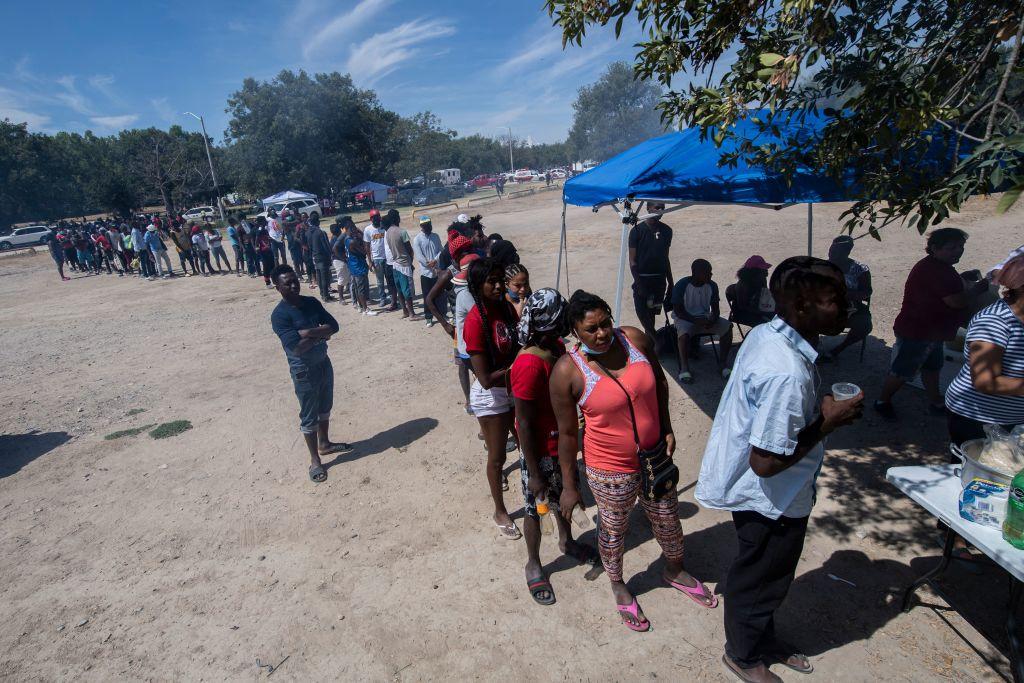 Migrantes esperan en una fila para recibir comida en Ciudad Acuña